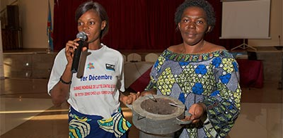 Josephine Malimukono with Joyce, giving clean energy presentation of stove to improve women's access to energy and reduce the risk of gender based violence associated with collecting wood.