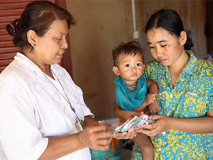 A medical professional explains to a young woman, holding a baby, how to take her pills