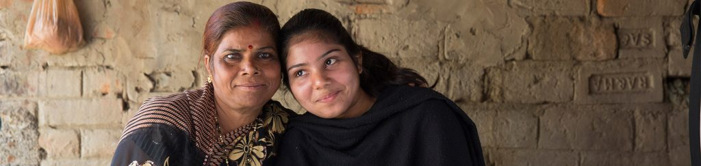 An Indian woman and her niece, a survivor of domestic violence, embrace