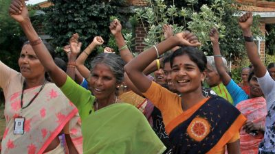 Indian women lift their arms in a cheer