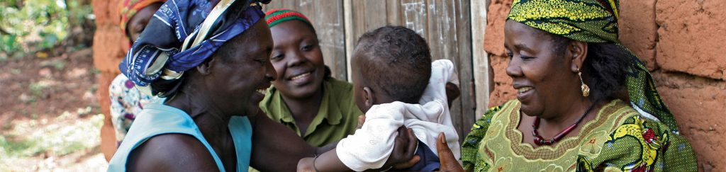 Three women in Sub-Saharan Africa laugh with a baby.
