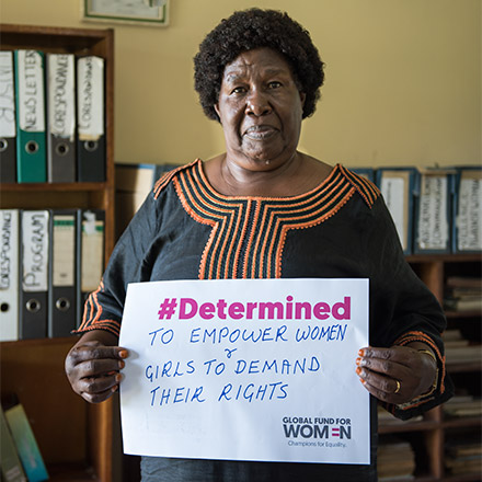Alupo holding a sign: #Determined to empower women and girls to demand their rights
