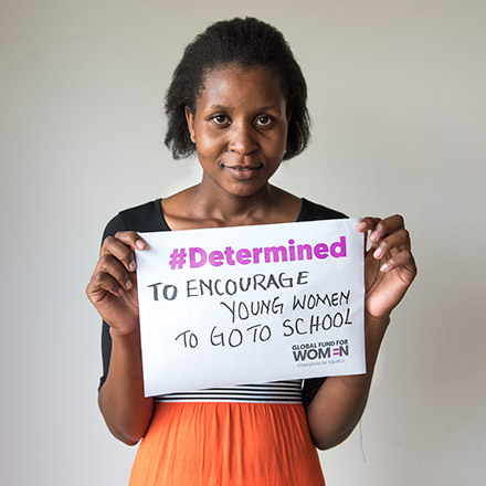 Cynthia holding a sign: #Determined to encourage young women to go to school