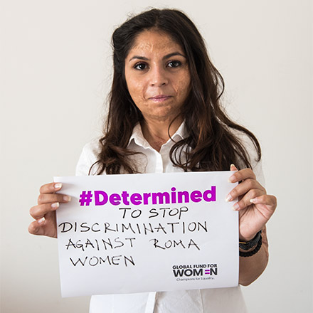 Milica with a sign: #Determined to stop discrimination against Roma women