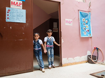 Two little girls at a doorway at the Shatila camp