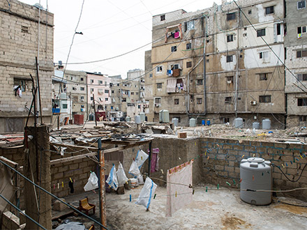 Exterior view of the Shatila camp, showing concrete barracks-like structures with hanging laundry